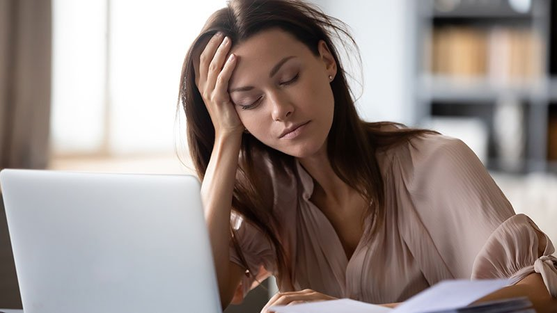 woman holding head in hand looking tired in front of computer