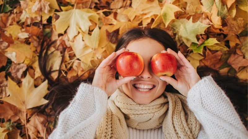 women laying in fall leaves putting apples to her eyes