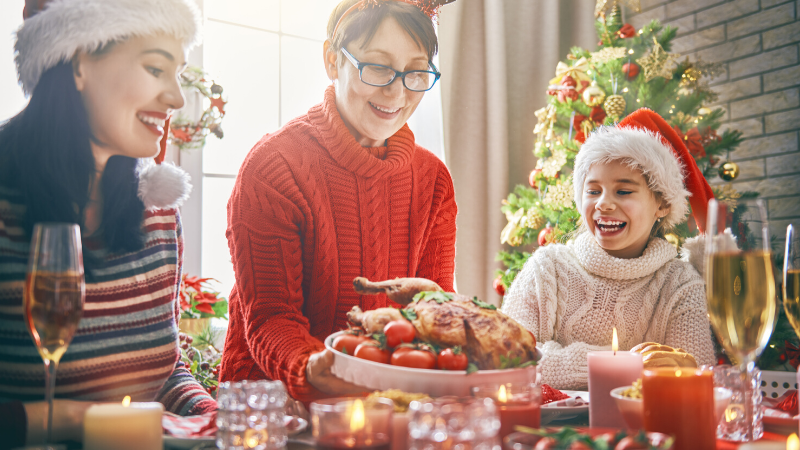 eating well during the holidays - family sitting at a table about to eat a holiday dinner.'