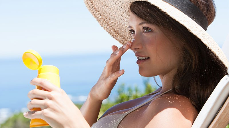 woman sitting outside in a chair with a hat on putting sunscreen on her nose