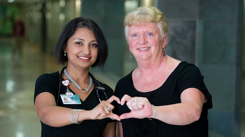 Sam Setty, MD and Deb Saphner creating heart with hands