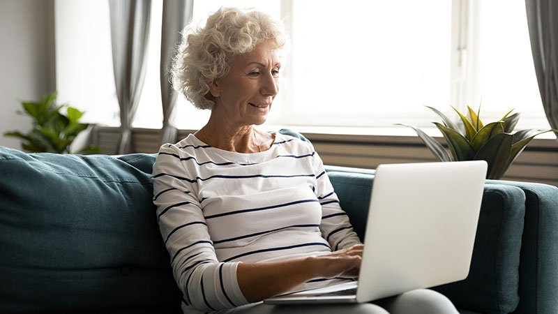 older woman sitting on couch with laptop