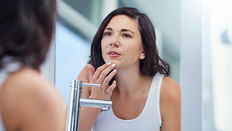 woman looking in the mirror at acne scars