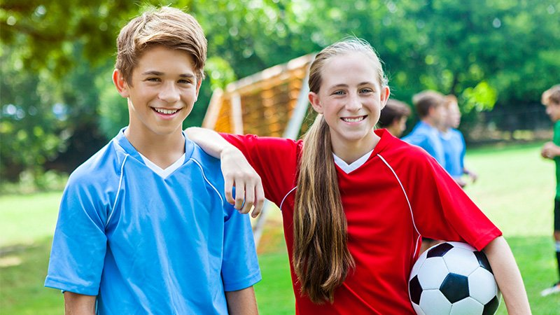 a boy and girl smiling with a soccer ball