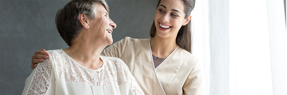 a certified nursing assistant smiling with patient