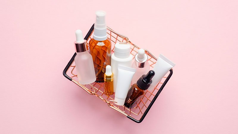 basket of skincare products on a pink background