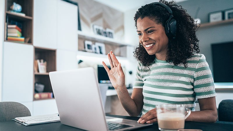 woman with headphones on waving at her computer