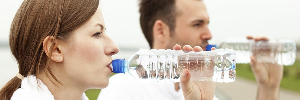Man and woman drinking bottled water