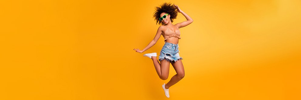 woman jumping and happy on an orange backgroudn
