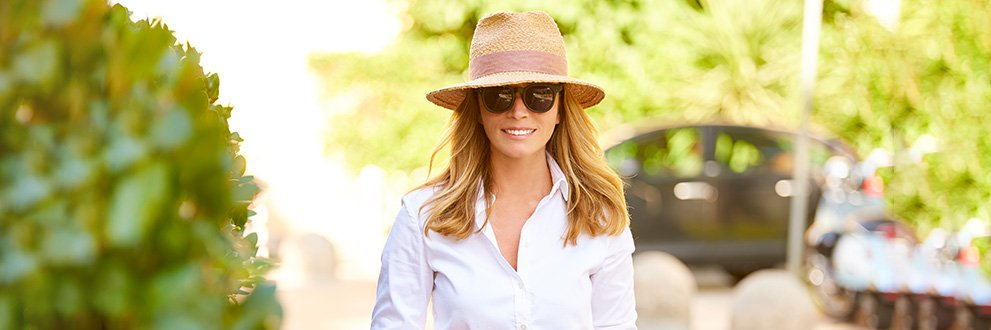 a woman smiling in a hat outside in the sun