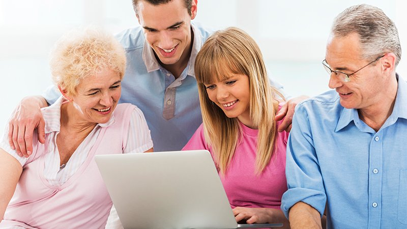 family smiling looking at a computer screen