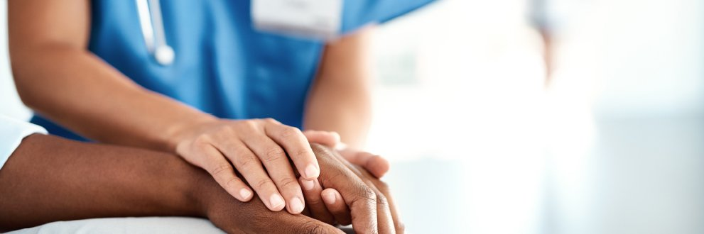 closeup of a nurse holding a patient's hand