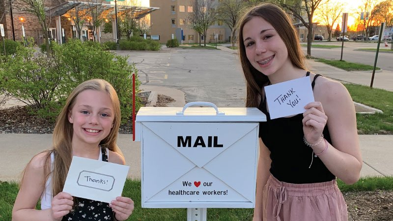 two girls outside of thank you mailbox with cards
