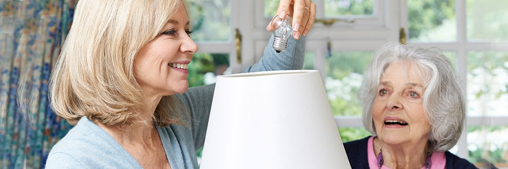 woman changing light bulb for family member