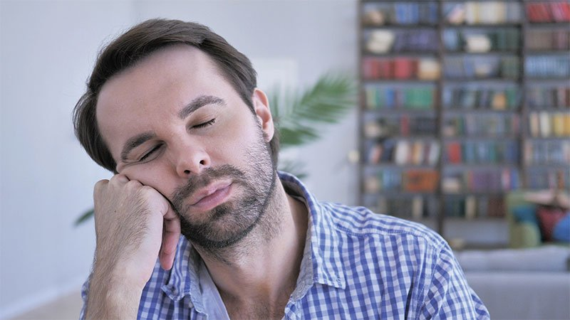 man resting head on hand with eyes closed