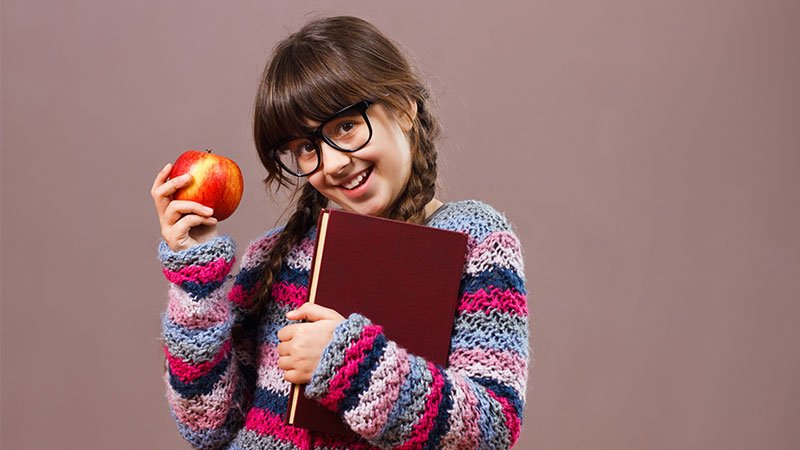 girl in glasses smiling holding an apple in one had and a book in the other