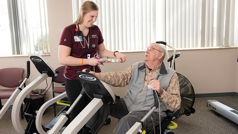 Exercise physiologist Kelsey Paarmann, MS, works with patient Robert Middleton in Cardiac Rehab.