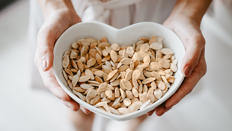 Woman holding a heart shaped bowl of roasted pumpkin seeds