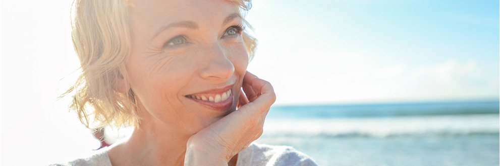 mature woman smiling at the beach