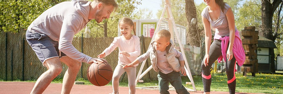 two parents playing basketball with children