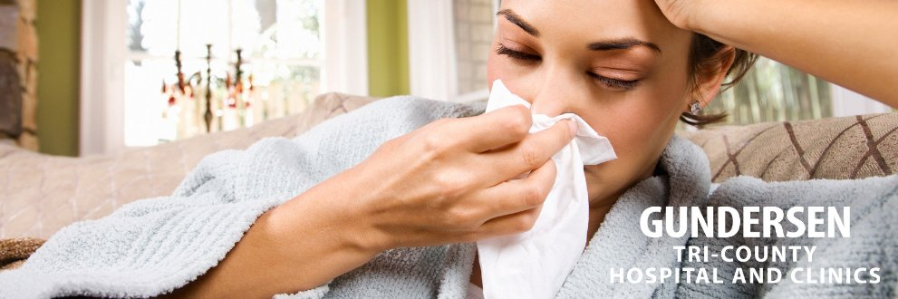 woman sick on couch blowing her nose