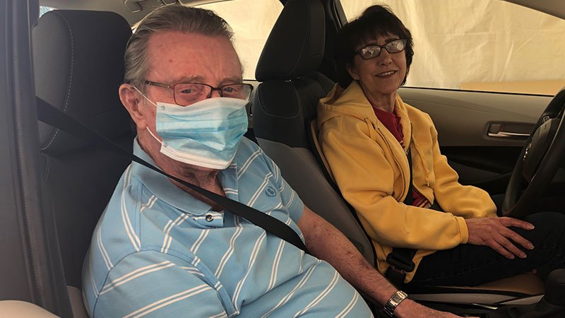 man with wife in car for drive-up lab