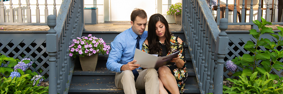 young couple sitting on steps looking at folder