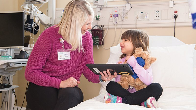A child life specialist shows girl something on tablet