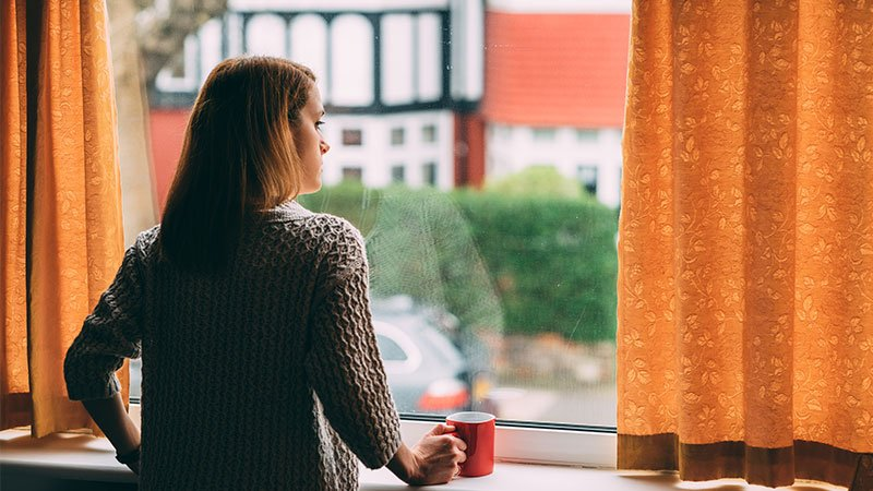 Woman looking out the window of her home