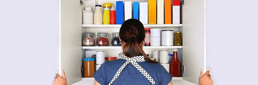woman cleaning out cupboard