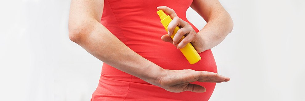 pregnant woman spraying repellent